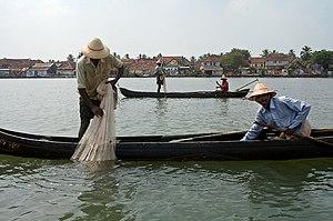 Vissermanne trek 'n net op 'n kano in indië