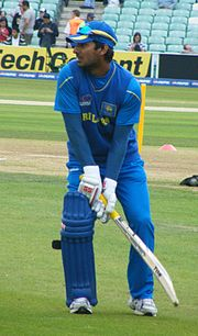 A side view of Kumar Sangakkara in blue clothes, holding a bat against the background of green grass and light yellow pitch.