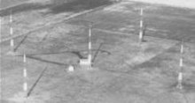 Aerial view of five tall Adcock antenna towers standing on flat terrain; four are arranged in a square, and the fifth one is at the center