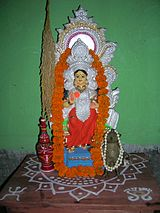 Alpana on an altar underneath a statue of the goddess Lakshmi