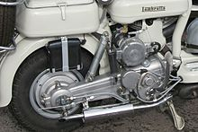 The image shows the starboard side (right side when facing forward) of the suspension of a Lambretta Model C. The swingarm, spring/damper unit, and wheel are shown.