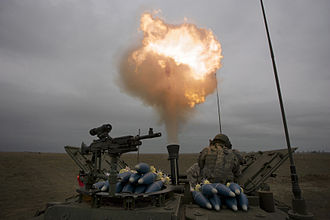 Muzzle flash - Soldiers covering their ears while firing a 120-mm mortar
