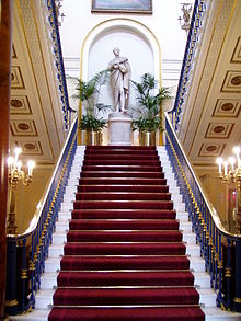 A red-carpeted staircase seen centrally from below with banisters on each side.  At the top is a statue of a standing man wearing a toga and holding a scroll, and on each side are chandeliers on stands