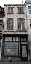 Huis met smalle lijstgevel, met segmentboogvensters, ten dele in Naamse steen.