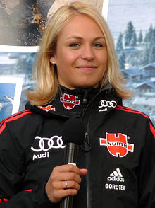 A blonde woman shown from the waist up in a predominantly black jacket, holding a black microphone, looks towards the camera and smiles slightly.
