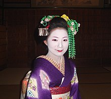A maiko wearing a purple kimono and a long green hair ornament on her left side