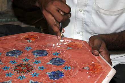 An Agra craftsman working with marble stone inlays. The marble is coloured red to give contrast while working. Marbleworks-1.jpg