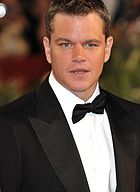 Matt Damon, a caucasian male in his late-30s with dark hair, looks into the camera. He wears a black suit and white shirt with a black bow-tie.