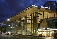 An outside, night-time shot of the building. It is well lit and has almost full-length glass panels. At the right side is the name of the drama school and also the lettering for Parade Theatres. An interior stairway is visible on the left side and a rounded wooden structure at right.