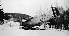 A black-and-white photo of a biplane sitting on the ground, shown in semi profile, viewed from the left-rear. The left wing and nose is buried in the ground.