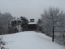 The brick building from the coin. It is seen at a distance, and snow covers the ground.