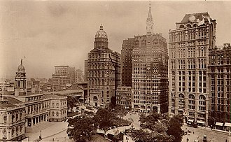 Park Row (Manhattan) - Park Row after 1905. Buildings from bottom left clockwise are: New York City Hall; the New York World Building, also known as the Pulitzer Building (with spherical top) which housed the New York World newspaper (now the site of one of the Brooklyn Bridge entrance ramps); the 1873 New Yorker Staats-Zeitung Building, also later demolished; the New York Tribune Building with the spire top (today the site of the Pace Plaza complex of Pace University); the New York Times Building (19th century home of The New York Times, today a building of Pace University); and, cut off from the picture, the Potter Building.