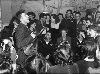American folk-music revival - Pete Seeger entertaining Eleanor Roosevelt, honored guest at a racially integrated Valentine's Day party marking the opening a Canteen of the United Federal Labor, CIO, in then-segregated Washington, D.C. Photographed by Joseph Horne for the Office of War Information, 1944.