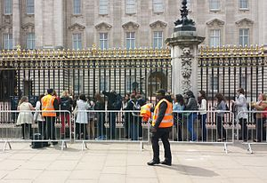 Princess Charlotte of Cambridge - The queue outside Buckingham Palace, London, to view the official announcement of the birth of Princess Charlotte at 13:15 on 2 May 2015. The ornate golden easel holding the announcement is just visible behind the railing, centre left.