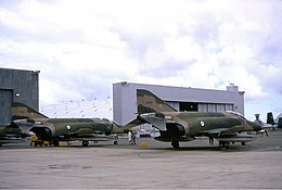 Two military jet fighters painted in camouflage livery parked in front of a large white building