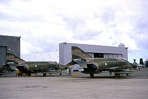 Colour photo of two military jet fighters painted in a camouflage pattern parked in front of a large white building
