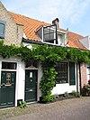 foto van Hoekpand Langepoortstraat. Schilderachtige, witgepleisterde lijstgevel voor huis van parterre en zadeldak