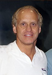 A man wearing a white polo looks straight ahead.