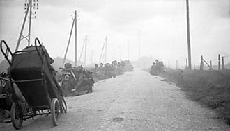 4th Special Service Brigade - Canadian infantry wait in ditches, as 48 RM Commando take cover from mortar fire on the roadside near St Aubin sur Mer