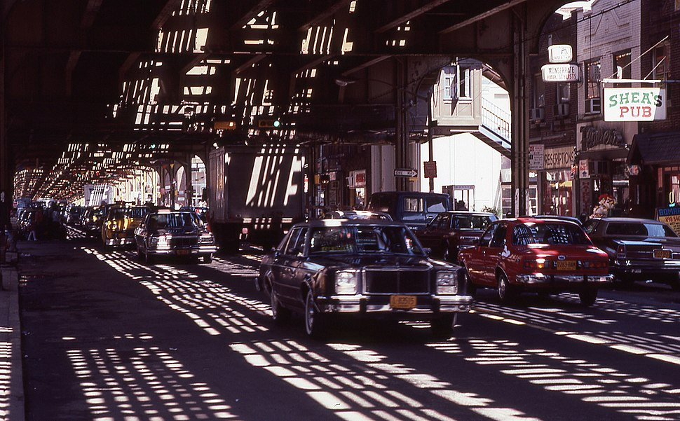 Roosevelt-avenue-queens-nyc cars driving-under-elevated-railway-line 1980s