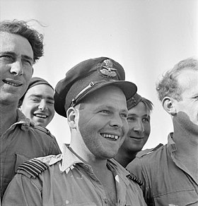 Informal head-and-shoulders portrait of grinning man in peaked cap surrounded by four others