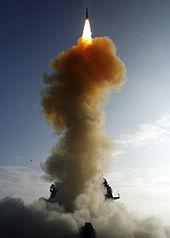 На вершине, темная ракета излучает яркий шлейф пламени против голубого неба.  Внизу, колонна дыма, частично скрывая военный корабль.