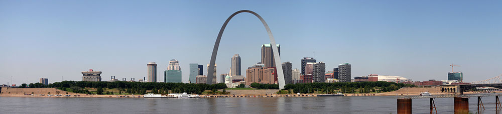 A large arch is in the center, across from a river. A clump of tall buildings is scattered behind it.