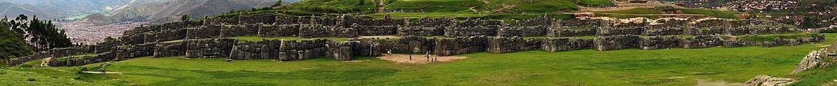 Sacsayhuamán'da insanlara oranla dev boyutlardaki taş duvarların genel görünüşü ve arka planda Cusco manzarası