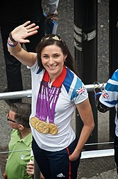 A Caucasian woman with brunette hair waves to a crowd. She is wearing a white polo shirt with the Union Jack flag on the left shoulder. Around her neck hang four Olympic gold medals.