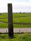foto van Op de dijk naar Warder een grenspaal in de vorm van een obelisk