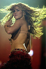 Shakira wearing a beige bra and a red skirt, with her hair twirling mid-dance