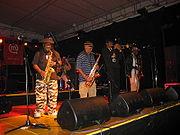 "Parte de la formación actual de Skatalites. De izquierda a derecha Lester ""Ska"" Sterling (saxo alto), Karl ""Cannonball"" Bryan (saxo tenor), Kevin Batchelor (trompeta) & Vin ""Don Drummond Jr."" Gordon (trombón). En segundo plano Val Douglas (bajo)."