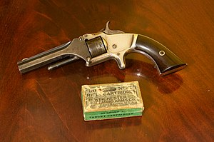 Револьвер Smith & Wesson Модель 1, другий випуск. This is a two patent date variety shown next to a period box of .22 short black powder cartridges.