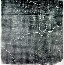 An image, probably a printout of a photograph, of a map of eastern China, complete with rivers. The area of the map covered by land features a near perfect grid pattern, which because it does not overlap any text, is clearly the work of the original mapmaker.