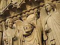 Statues of Saint Denis holding his head and two angel, Notre-Dame Cathedral, Paris 19 February 2007.jpg
