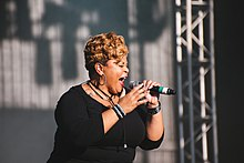 Tamela Mann sings into a microphone she is holding.