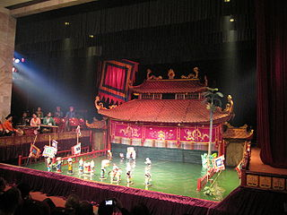 puppetry tradition from 11th century Red River Delta area of northern Vietnam, in which wooden lacquered puppets, supported by a bamboo rod, are moved around by puppeteers hidden behind a screen, appearing move over the water