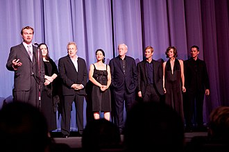 The Dark Knight (film) - Cast and crew of The Dark Knight at the European premiere in London. From left to right: Director Christopher Nolan, producers Emma Thomas and Charles Roven, actors Monique Gabriela Curnen, Michael Caine, Aaron Eckhart, Maggie Gyllenhaal and Christian Bale.
