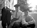 Tre pojkar med skärmmössor, knäbyxor, skjorta,och slips sitter på en balkong - Nordiska Museet - NMA.0057530.jpg