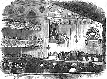 The interior of an elegant concert hall, an elegant audience, and on the stage, many men participating in the ceremony.