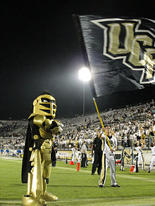 UCF's black and gold clad mascot, Knightro, on the field during a football game.