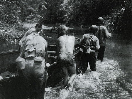 U.S. Army soldiers push supplies up the Matanikau River to support the 25th Infantry Division's offensive on Guadalcanal in January 1943.