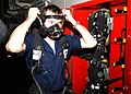 US Navy 021102-N-6817C-005 Damage Controlman Fireman Aaron Williams, of Amarillo, Texas, checks for the proper fit on a face mask on a Self Contained Breathing Apparatus (SCBA).jpg
