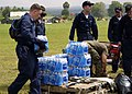 US Navy 050103-N-0057P-341 Sailors, assigned to USS Abraham Lincoln (CVN 72) and embarked Carrier Air Wing Two (CVW-2), stack bottled water prior to distribution to Tsunami victims in Aceh, Sumatra, Indonesia.jpg