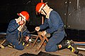US Navy 061101-N-5455M-012 Damage Controlman 3rd Class Thomas Abadie and Damage Controlman Fireman Anthony Abrao work together to obtain all necessary gear required to patch a simulated broken pipe.jpg