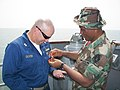 US Navy 070321-N-3621S-001 Lt. Martin Oliver, a prior enlisted naval diver, trades dive pins with a Cameroon Naval Dive Officer aboard USS Kauffman (FFG 59) during a daylong passing exercise (PASSEX) held off the coast of Limbe.jpg