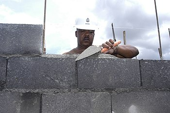 LIGAO, Philippines (June 26, 2007) - Senior Chief Builder James Brooks, attached to Naval Mobile Construction Battalion 7, carefully places mortar on a concrete block on a house being built in support of Pacific Partnership 2007. More than 50 Sailors contributed to the project with an aim to complete 35 new houses. A detachment of Seabees from NMCB-7 is attached to amphibious assault ship USS Peleliu (LHA 5) to assist the Philippine government in selected construction and engineering projects. U.S. Navy photo by Mass Communication Specialist Seaman Matthew Jackson .