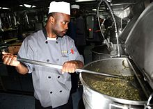 US Navy 081127-N-7571S-011 Culinary Specialist Seaman Freddie Green prepares collard greens for the crew's Thanksgiving dinner.jpg