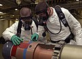 US Navy 090915-N-9915J-016 Gunners Mate 3rd Class Andrew Fournier, left, and Aviation Ordnanceman 3rd Class Randy Walther inspects a Mark 46 recoverable exercise torpedo in a weapons magazine aboard the aircraft carrier USS Ent.jpg