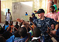 US Navy 100408-N-6138K-237 Musician 2nd Class Justin Strauss, a member of the U.S. Naval Forces Europe Band, Five Star Brass Quintet, high-fives children following a performance at the Colin Powell Cultural Center.jpg